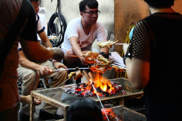People sit around charcoal fire pit, roasting meats. Location: Tai Hang Fire Dragon Dance, Tai Hang, Hong Kong | September 27, 2015 | Tanya McGovern