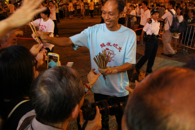 Man hands out joss sticks to the crowd. | Tai Hang Fire Dragon Dance, Tai Hang, Hong Kong | September 27, 2015 | Tanya McGovern