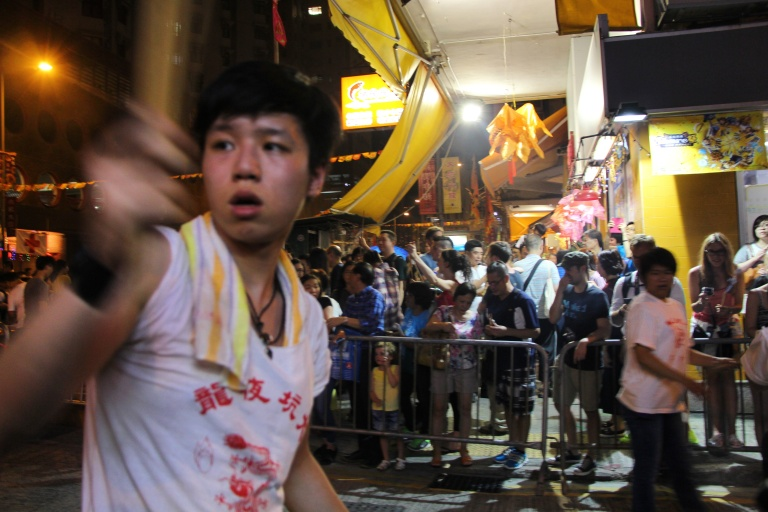 Fire dragon performer hands out joss sticks to crowd. | Tai Hang Fire Dragon Dance, Tai Hang, Hong Kong | September 27, 2015 | Tanya McGovern