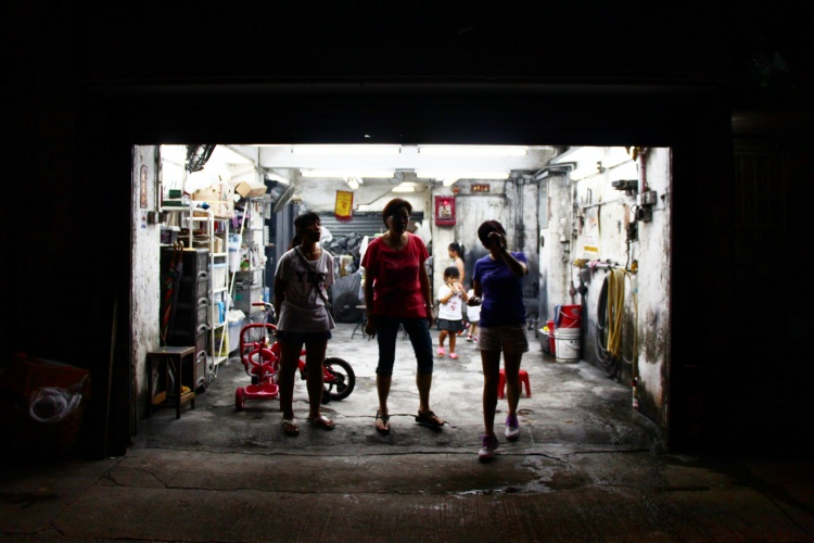 Women and children watch crowds move through the streets of Tai Hang, chasing the moving fire dragon, from garage. | Tai Hang Fire Dragon Dance, Tai Hang, Hong Kong | September 27, 2015 | Tanya McGovern