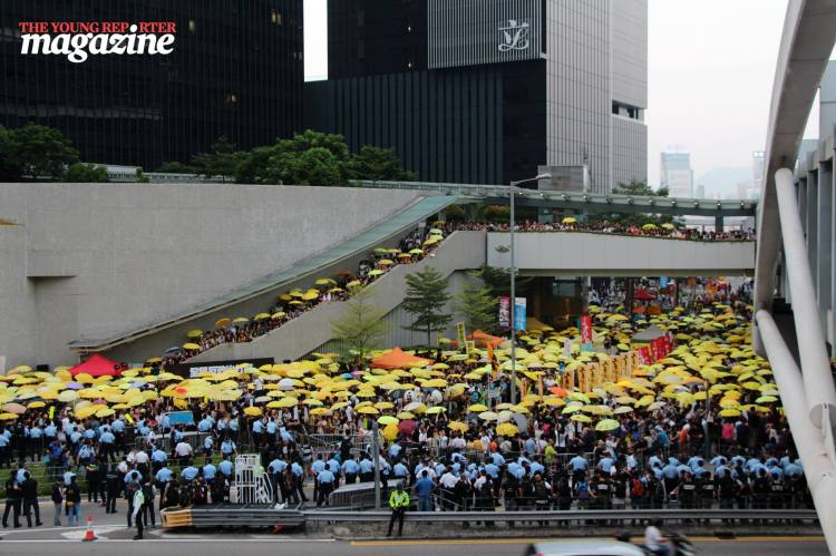 Protestors gather with yellow umbrellas at 5.58pm on Tim Ma Avenue to mark the moment pepper spray was used on crowds last year | Legislative Council Complex | September 28, 2015 | Tanya McGovern