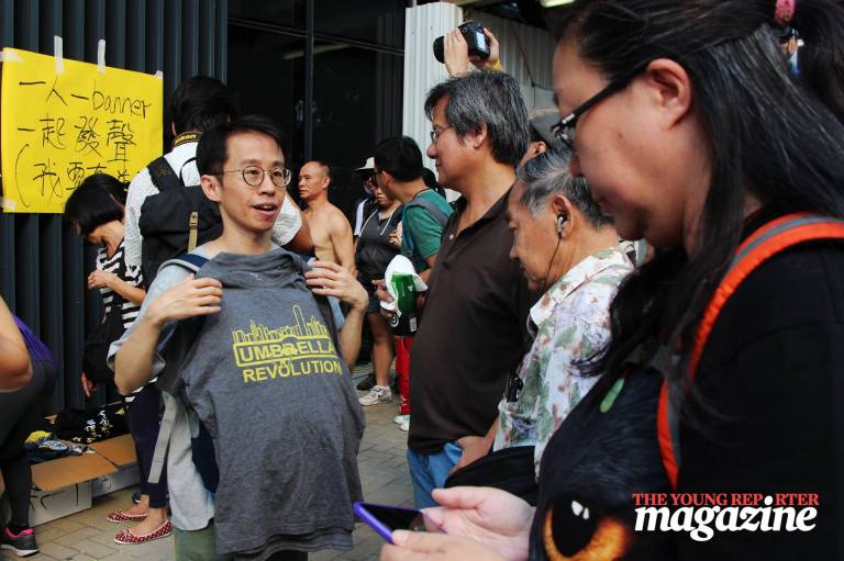 Man holds up a free t-shirt commemorating the Umbrella Movement | Legislative Council Complex | September 28, 2015 | Tanya McGovern