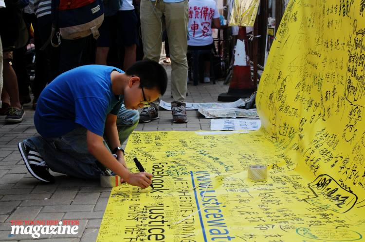 Boy signs a message on a banner campaigning for justice. | Legislative Council Complex | September 28, 2015 | Tanya McGovern