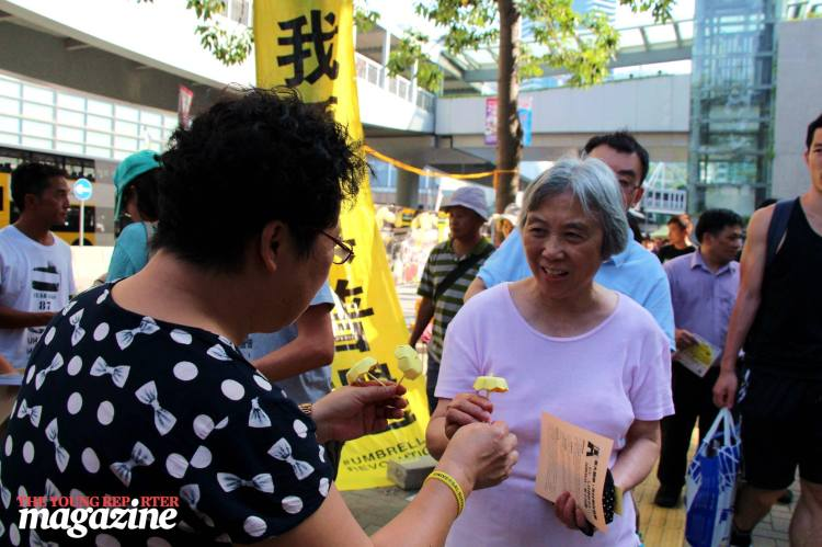 Woman hands out yellow umbrellas made of paper to passersby. | Legislative Council Complex | September 28, 2015 | Tanya McGovern