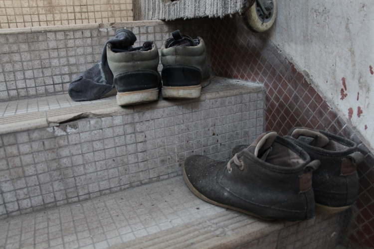 Shoes are left on the staircase to the building rooftop. | Tanya McGovern